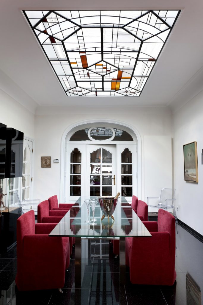 """Artglas"" designed a contemporary stained-glass window for an old mansion in Tongeren. The designers had to take into account the existing iron framework. To maximize incoming daylight, they opted for clear glass with many different structures. They mounted dim lights between the glass panel and the skylight, so that the residents can enjoy their beautiful stained glass in the evenings as well. Courtesy ""Artglas""."